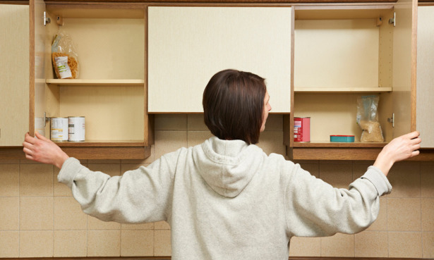 Someone opening empty kitchen cupboards