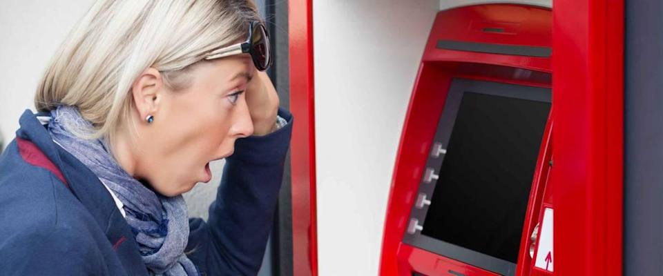 Shocked woman looking at her bank account balance